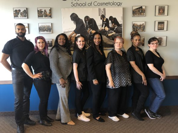 Corinthian Carouthers (center) pictured with the administrative and educational team at Creative Hair School of Cosmetology